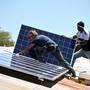 Placement des premiers panneaux solaires sur le toit des classes.